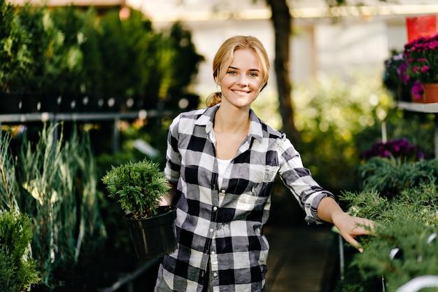 Красивая женщина в милой одежде тянется к растениям в теплице