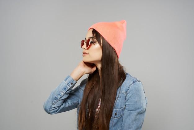 デニムシャツサングラスピンクの帽子のきれいな女性のポーズファッション灰色の背景スタジオ