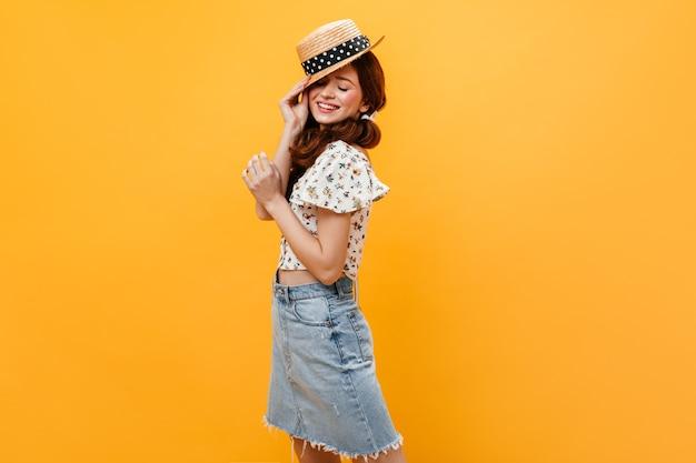 Симпатичная женщина в джинсовой юбке и легком укороченном топе надевает канотье и улыбается. Бесплатные Фотографии