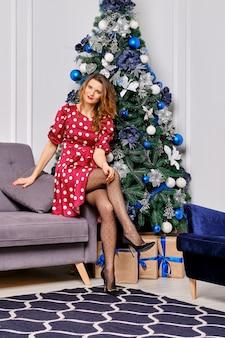 점선 실크 드레스와 폴카 도트 스타킹에 예쁜 여자가 크리스마스 트리 근처 소파에 앉아있다.
