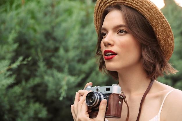 Красивая женщина в платье и соломенной шляпе делает фото на ретро-камеру, глядя в сторону на открытом воздухе