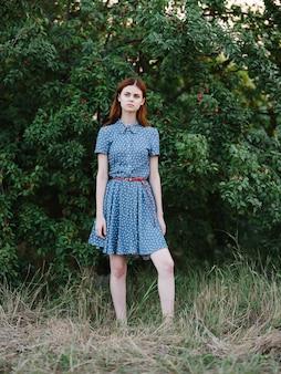 緑の茂みの自然をポーズする赤い髪のドレスのきれいな女性