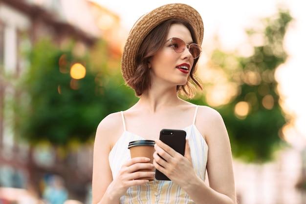 Красивая женщина в платье, соломенной шляпе и солнцезащитных очках позирует с чашкой кофе и смартфоном, глядя в сторону на открытом воздухе