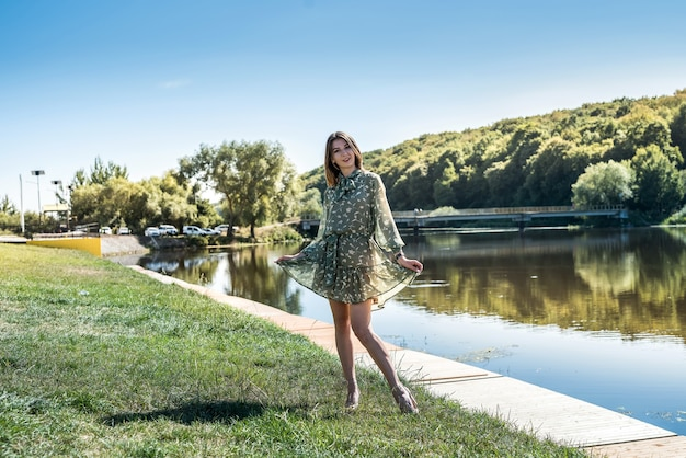 ドレスを着たきれいな女性が湖のそばに立っていて、自然の中でリラックスしてカメラに向かってポーズをとっていました
