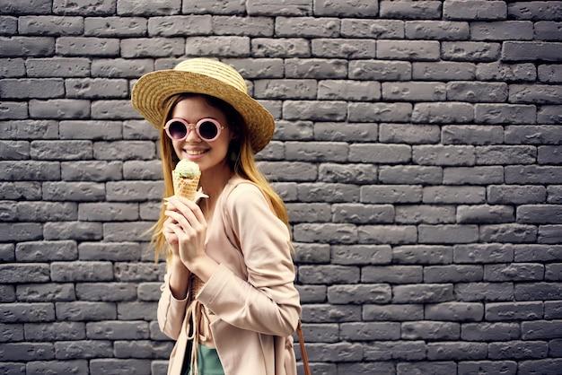 배경에 우아한 스타일 모자 야외 아이스크림 벽돌 벽에 예쁜 여자.