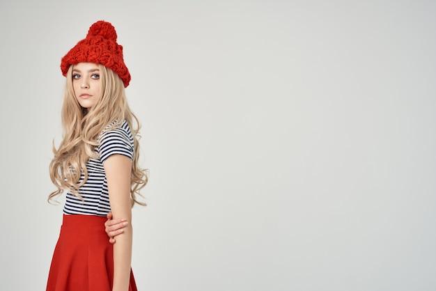 ファッショナブルな服を着たきれいな女性レッドハット明るい背景。高品質の写真