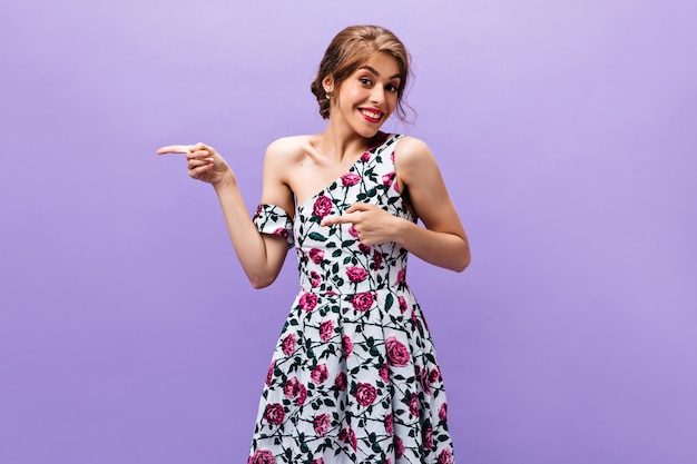 テキストの場所を指している花柄のドレスを着たきれいな女性。笑顔の夏服でクールな髪型の美しいファッショナブルな女の子。