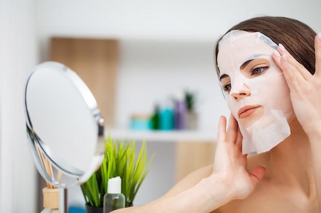 거울 앞에서 예쁜 여자는 피부 관리를 위해 얼굴에 마스크를 넣습니다.