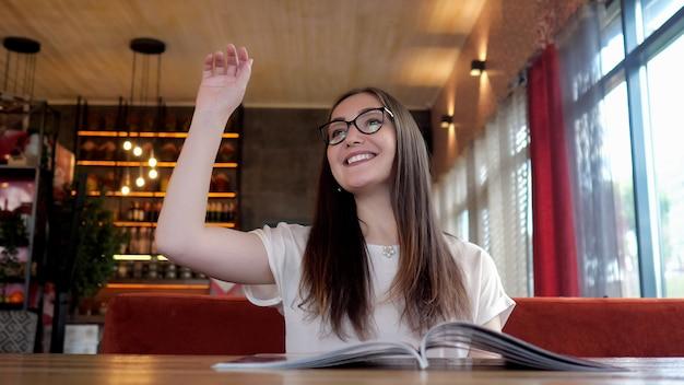 メニューを読んで注文するメガネのきれいな女性。