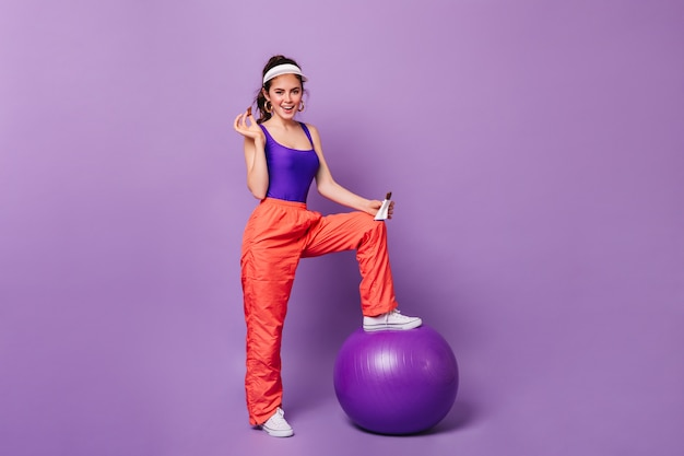 좋은 분위기의 예쁜 여자는 그녀의 발을 fitball에 넣고 보라색 벽에 초콜릿 바로 포즈를 취합니다.