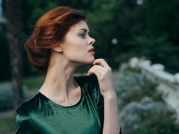 緑のドレスのきれいな女性が魅力的な外観の豪華な屋外モデル。