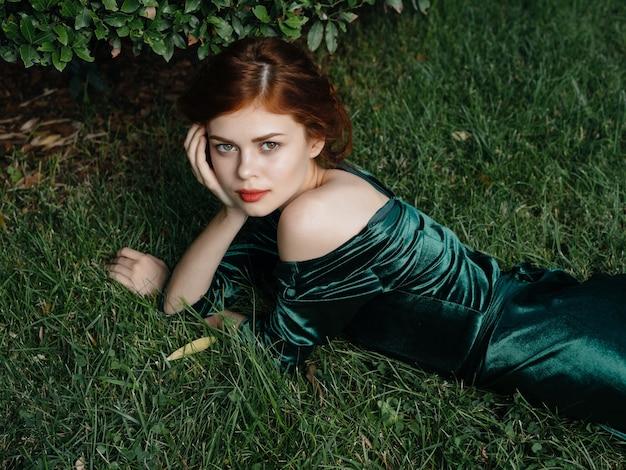 緑のドレスを着たきれいな女性は、ファンタジーガーデンの芝生の上に横たわっています