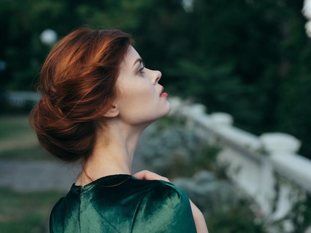 緑のドレスを着たきれいな女性が屋外で魅力的な外観の豪華さ。高品質の写真