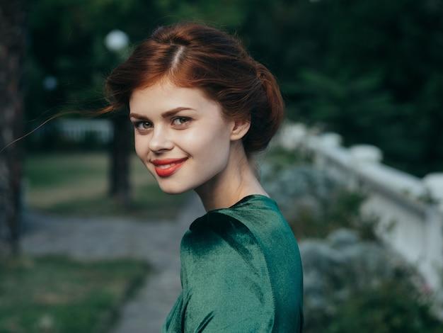 Красивая женщина в зеленом платье на открытом воздухе роскошный привлекательный вид.