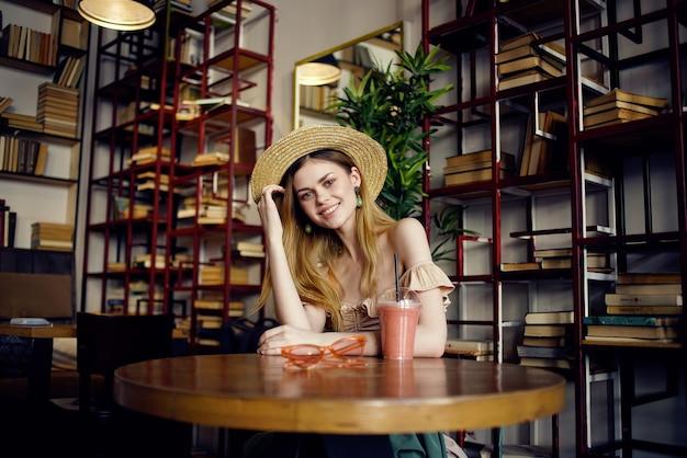カフェ休暇のライフスタイルでジュースを飲む帽子のきれいな女性。高品質の写真