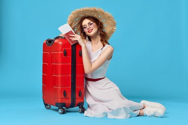 빨간 가방 여행 목적지와 함께 바닥에 앉아 모자에 예쁜 여자
