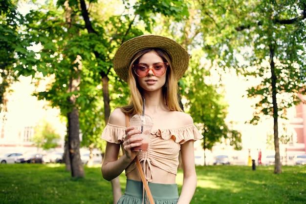 帽子をかぶったきれいな女性が夏の公園のレジャーで屋外を歩きます。高品質の写真