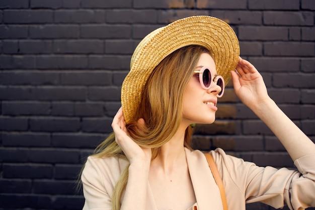 도시 벽돌 벽에 야외에서 선글라스를 쓰고 모자에 예쁜 여자