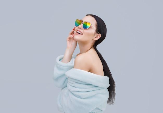 ハート型のレインボーサングラスをかけたきれいな女性が楽しい感情を表現