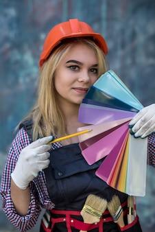 カラーパレットを保持し、家の修理の準備ができてヘルメットと制服を着たきれいな女性。家のデザイン