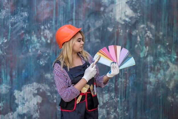 ヘルメットと制服を着たきれいな女性が家の修理の準備ができて、カラーパレットを保持しています