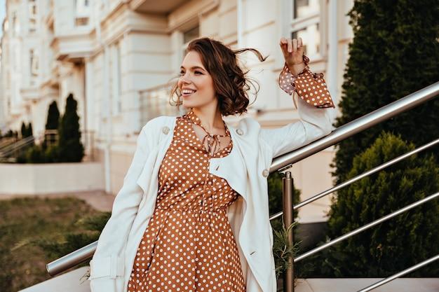 通りで笑っている長い茶色のドレスのきれいな女性。エレガントなメイクで感情的な女性モデルの屋外ショット。