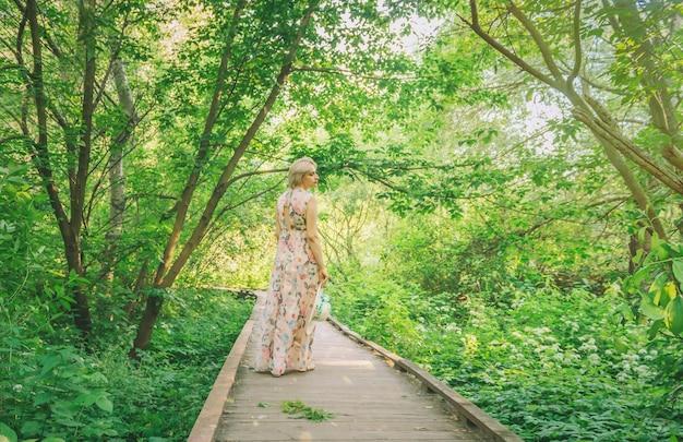 공원에서 여름 시즌에 긴 드레스에 예쁜 여자.