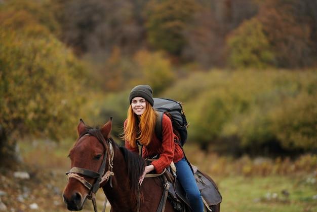 自然の中のきれいな女性は旅行で楽しい馬を歩きます。高品質の写真