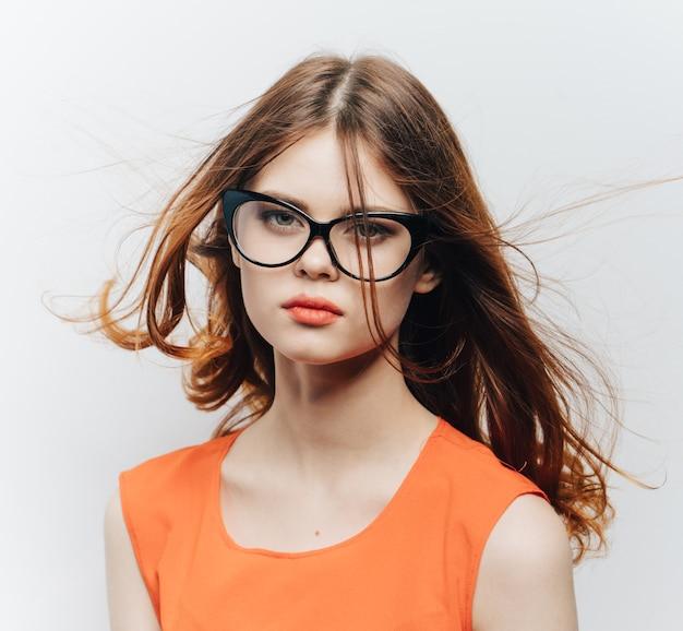 明るい背景のトリミングされたビューにオレンジ色のサンドレスとメガネのきれいな女性