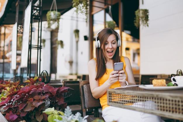 テーブルに座って、ヘッドフォンで音楽を聴き、携帯電話を使用して、自由時間にレストランでリラックスして、屋外のストリートコーヒーショップカフェのきれいな女性