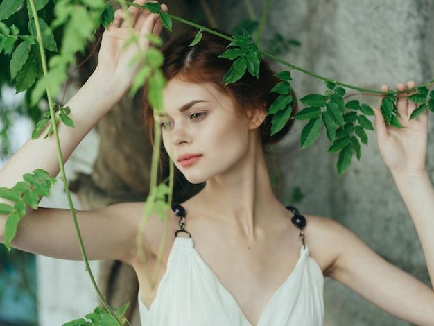 나무 돌담 포즈 신화 근처 공원에서 예쁜 예쁜 여자. 고품질 사진