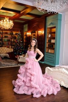 クリスマスツリーの近くのピンクのドレスのきれいな女性