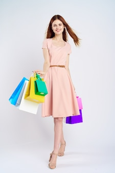 Красивая женщина в розовом платье, делая покупки пестротканые пакеты студии. фото высокого качества