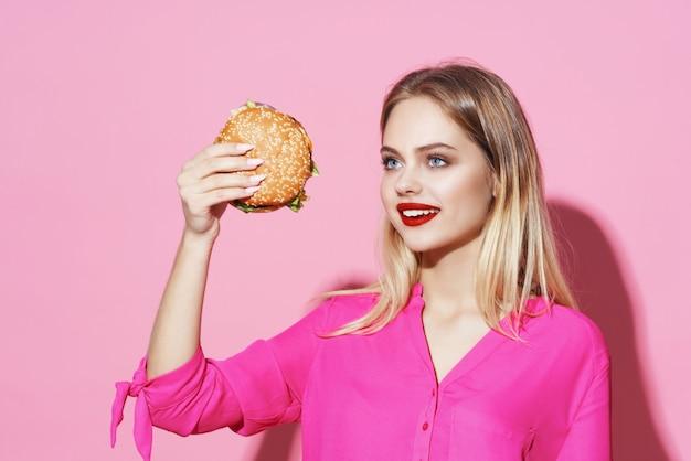 Красивая женщина в розовой рубашке с диетой быстрого питания гамбургер