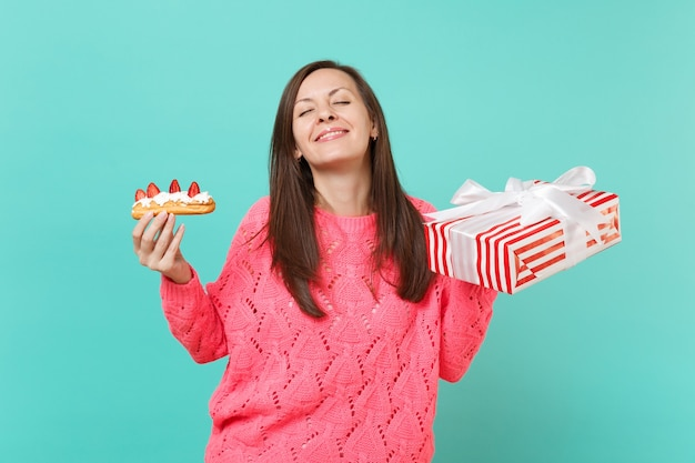 エクレアケーキ、青い背景で隔離のギフトリボンと赤いプレゼントボックスを保持している目を閉じてピンクのセーターのきれいな女性。バレンタイン、女性の日、誕生日の休日のコンセプト。コピースペースをモックアップします。