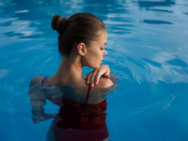 プールのきれいな女性赤い水着豪華な背面図のライフスタイル