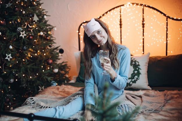 침대에 음료와 함께 잠 옷에 예쁜 여자입니다.