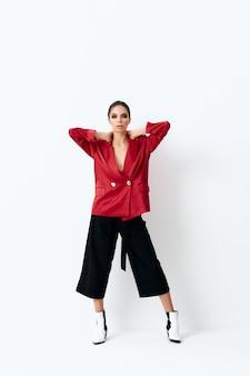 赤いブレザーのファッショナブルな服を着たきれいな女性はい首の魅力に手を差し伸べる