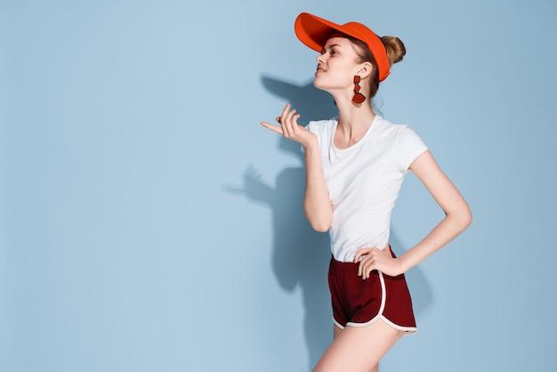 赤い帽子の装飾ファッション青い背景のきれいな女性