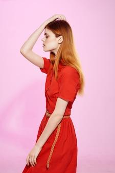 Красивая женщина в красном платье мода элегантный стиль розовый фон. фото высокого качества