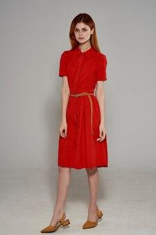 Красивая женщина в красном платье жесты рукой роскошной студии