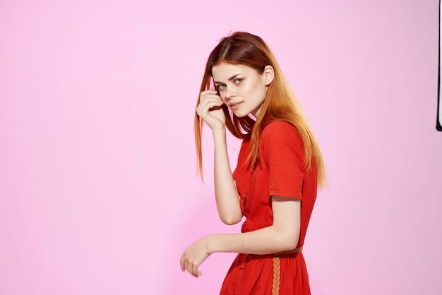 Красивая женщина в красном платье позирует на розовом фоне привлекательный вид. фото высокого качества
