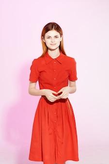 Красивая женщина в красном платье позирует привлекательный взгляд на розовом фоне