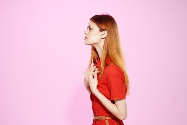 ファッションの贅沢をポーズする赤いドレスのきれいな女性