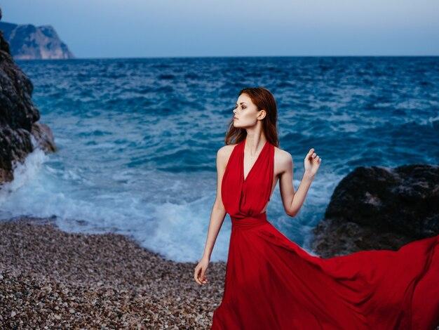 崖のビーチの休暇のロマンスの近くでポーズをとって赤いドレスを着たきれいな女性