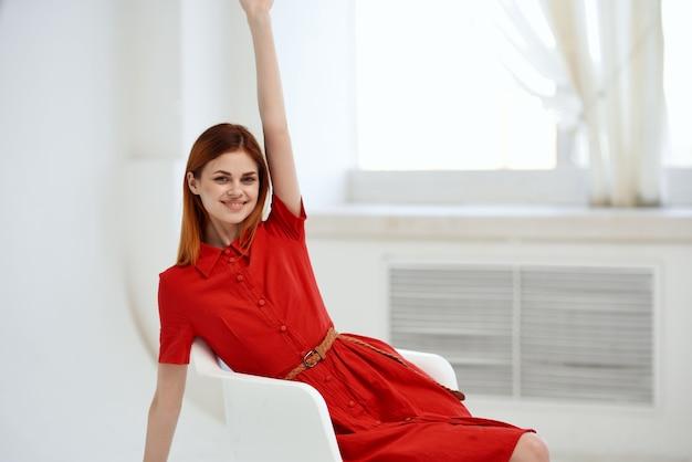 椅子の贅沢にポーズをとって赤いドレスを着たきれいな女性