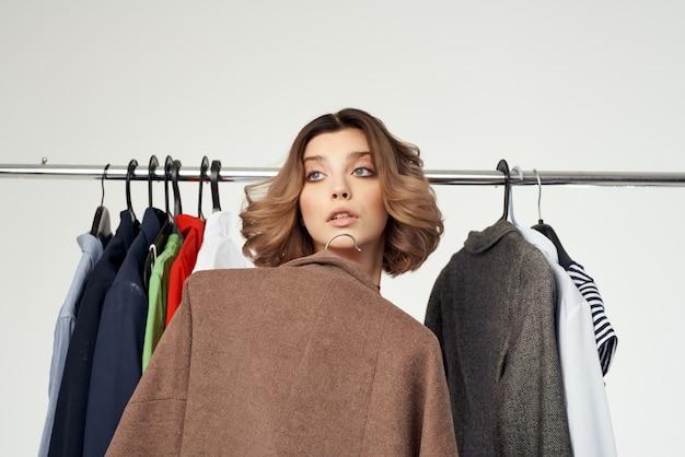 赤いドレス買い物中毒のきれいな女性が店の孤立した背景で買い物をする服を選ぶ