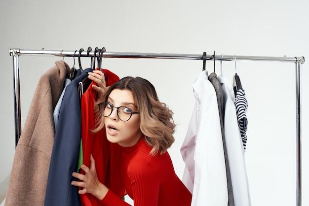 상점 스튜디오 생활 방식에서 쇼핑하는 옷을 고르는 빨간 드레스를 입은 예쁜 여자