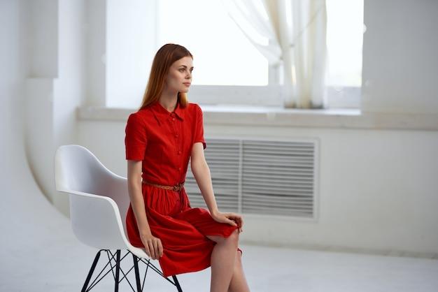 窓のファッションの近くに座っている赤いドレスのきれいな女性