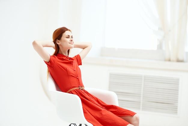 椅子のファッションに座っている赤いドレスのきれいな女性